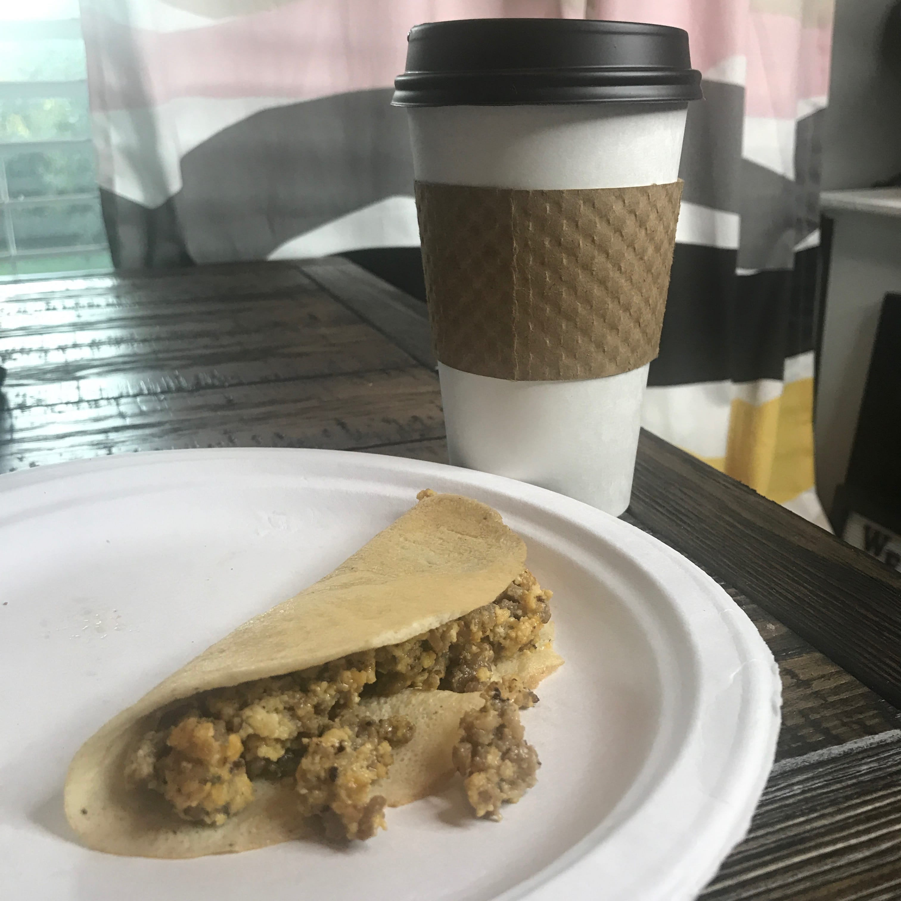 Keto Crepe filled with sausage egg and cheese sitting on a table with coffee